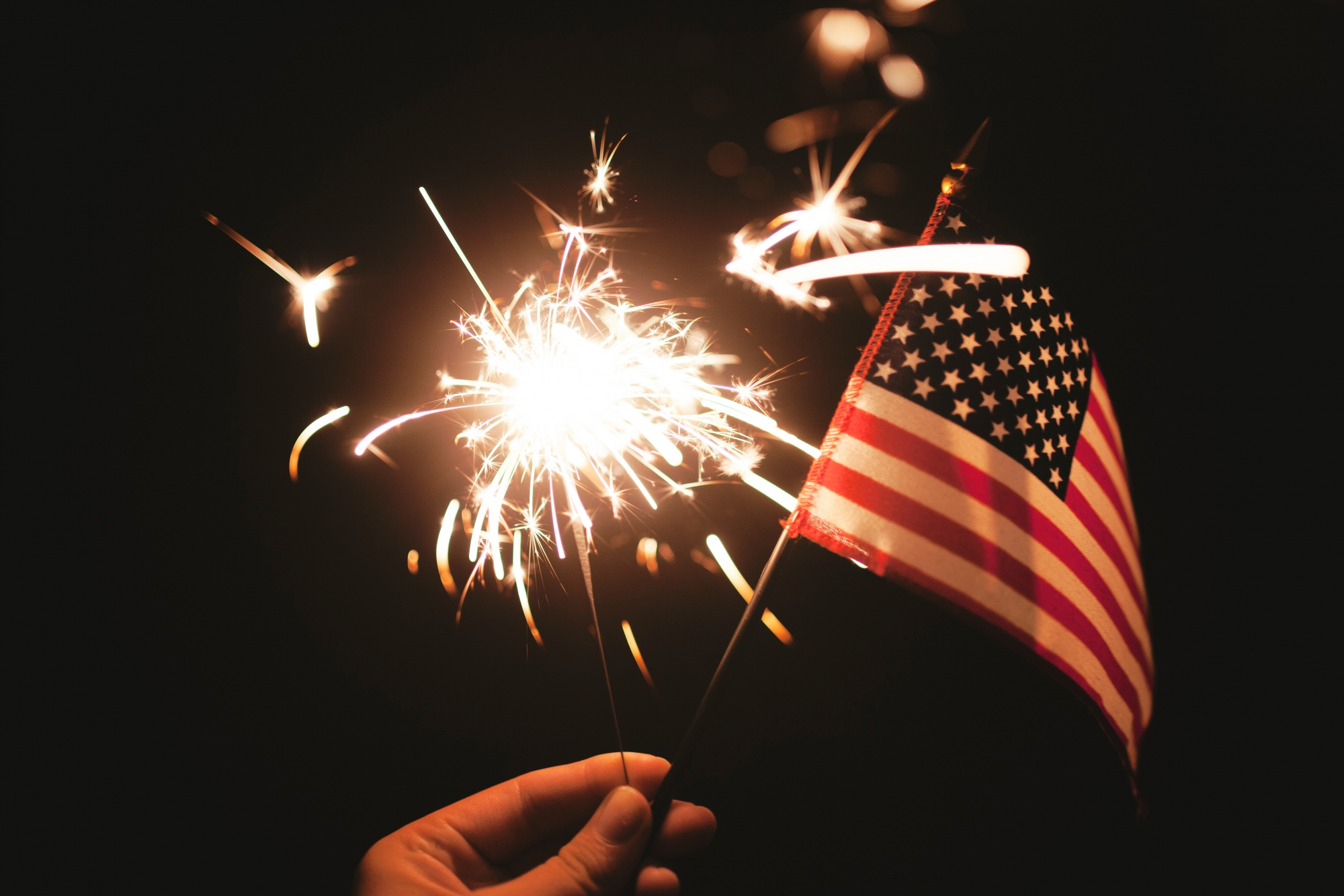 A hand holds a sparkler firework and a small Flag of the United States of America.