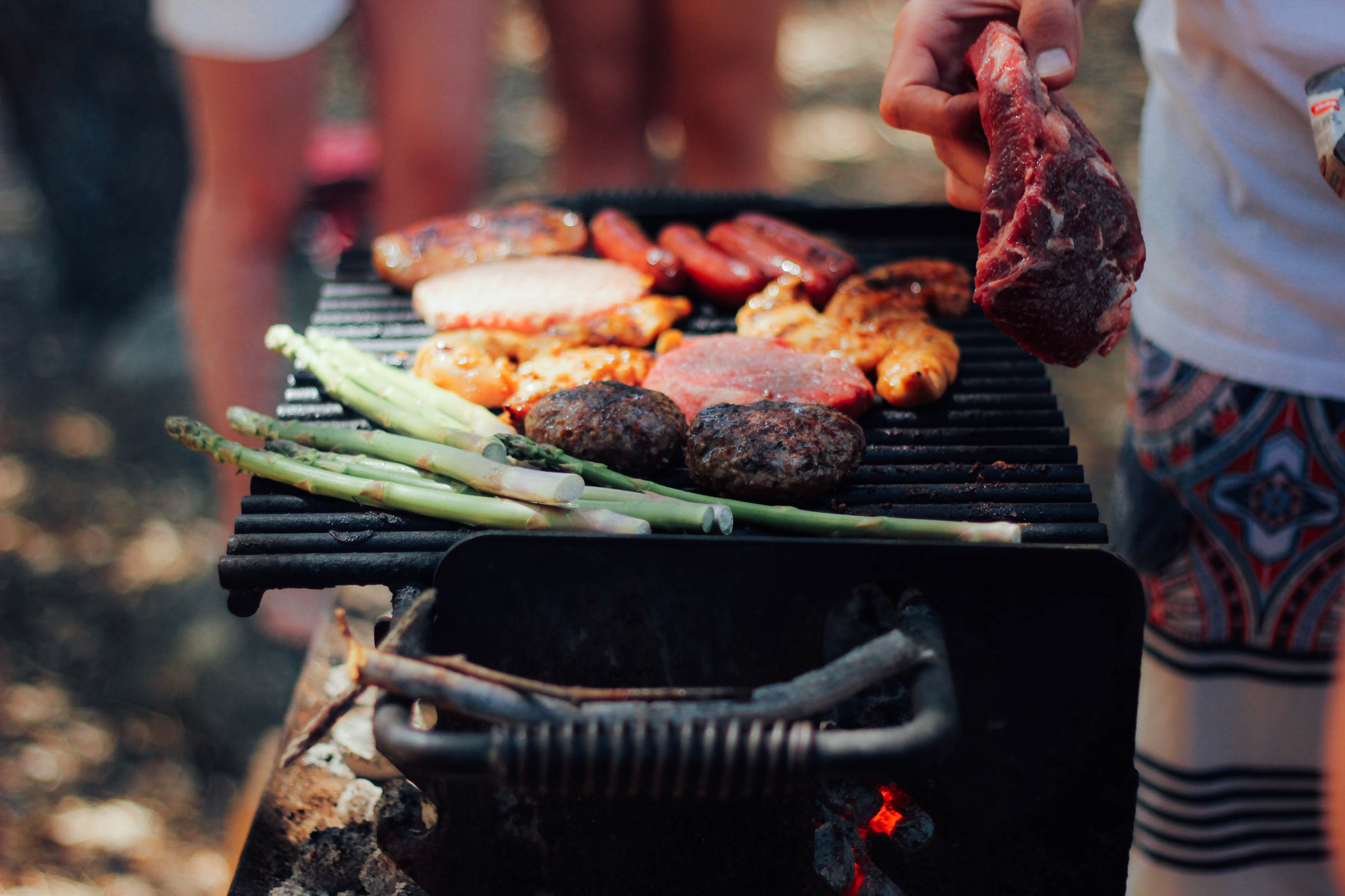 Someone prepares asparagus, steak, burgers, and hot dogs on a charcoal grill outside.